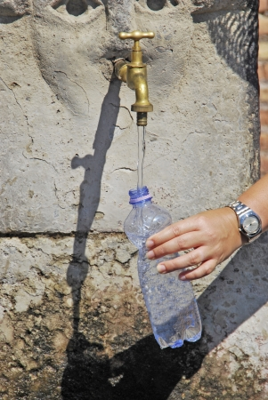 A hand is getting water in the faucet.  photo