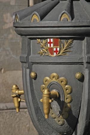 Old fashioned urban faucet with coat of arms in Barcelona. Spain. photo