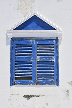 fira: Weathered window painted in blue. Fira, Santorini, Greece