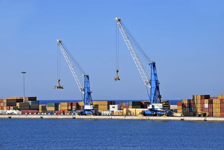 Two cranes and some containers at a commercial harbor photo