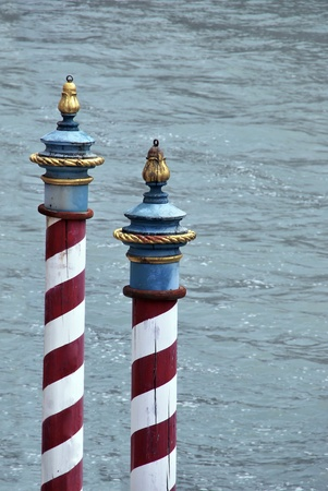 Typical striped poles for mooring boats in Venice. Italy photo