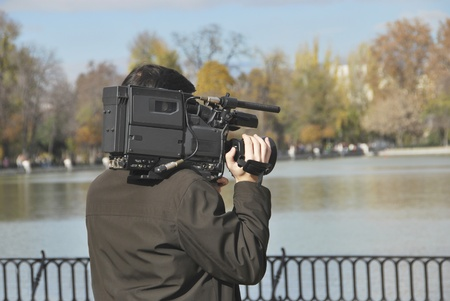 Cameraman operating a video camera with his hand photo