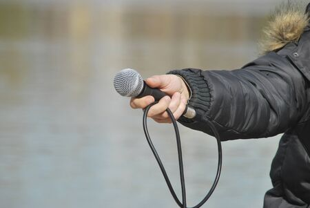 A hand is holding a microphone for an interview photo