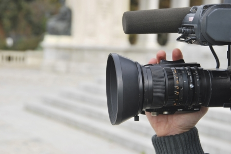 camera operator: A hand is operating a professional video camera  Stock Photo
