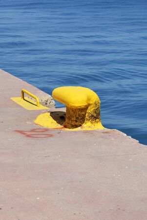 mooring: Iron pier painted in yellow in the harbor Stock Photo