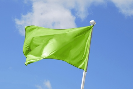 Green flag waving on the sky. Promotional and advertisement sign photo