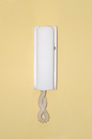 interphone: Home intercom on a wall painted in yellow Stock Photo
