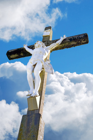 Statue of Jesus Christ crucified over a cloudy sky