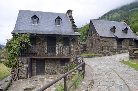 toran: Typical stone houses in Sant Joan de Toran, Valle de Aran, Lleida, Catalonia, Spain  Picture taken in a cloudy day