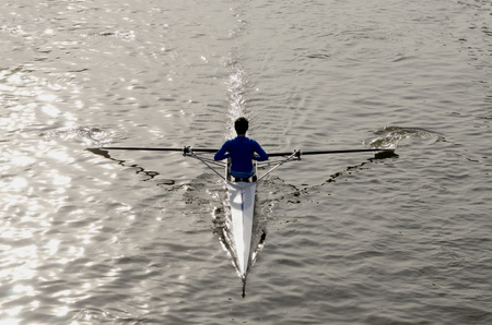 rower: A rower in a river viewed from backside Stock Photo