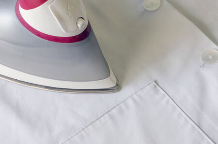 Detail of an steam iron over a white garment photo