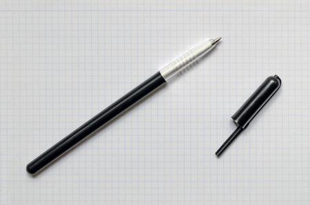 Black ballpen without cap over a graph paper photo