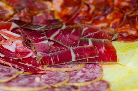 Iberian sausage slices an cheese on a plate