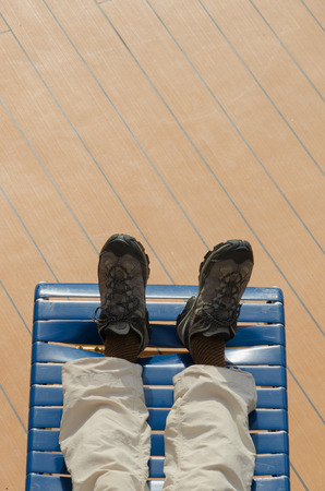 View of the feet of a man lying on a deck chair photo