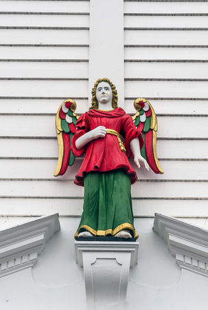 angel figurine: Wooden guardian angel blue eyed and painted in red, gold and green Stock Photo