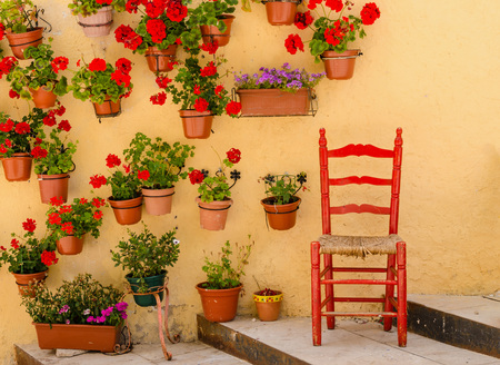 Rustic wooden chair painted in red surrounded of geranium pots. Spain Archivio Fotografico