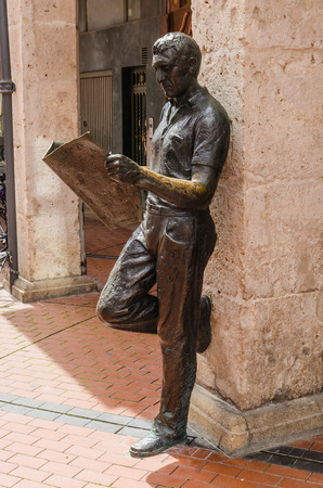 castile: Sculpture of a man leaning against a column and reading a newspaper. Burgos, Castile and Leon, Spain