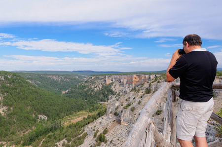 A man is looking trough binoculars. Rio Lobos Canyon. Soria, Spain