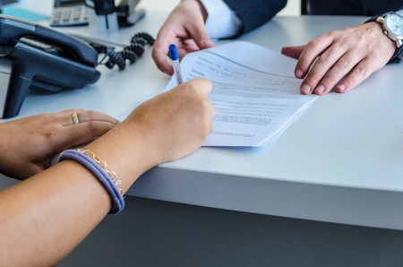 A woman is signing a purchase document photo