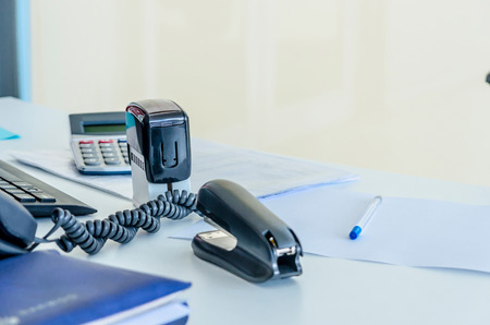 office stapler: An office workplace with a phone, stapler, documents, stamp; pen; calculator and a computer