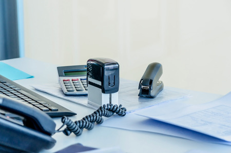 office stapler: An office workplace with a phone, stapler, documents, stamp; calculator and a computer Stock Photo