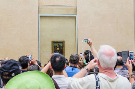 PARIS - SEPTEMBER, 17: Visitors take photo of Leonardo DaVincis Mona Lisa at the Louvre Museum on September, 2014 in Paris, France. Gioconda is one of the worlds most famous pictures in the world.