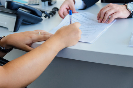 a woman signs a purchase document with a blue ballpen photo