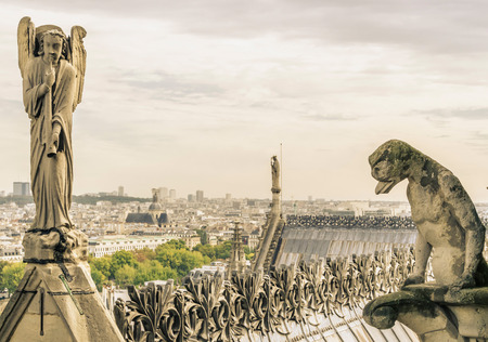 gargoyle: A gargoyle and an angel in Notre Dame. Vintage style photo