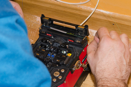 fibra óptica: La instalación de fibra óptica en el hogar. Fibra óptica fusionadora Foto de archivo