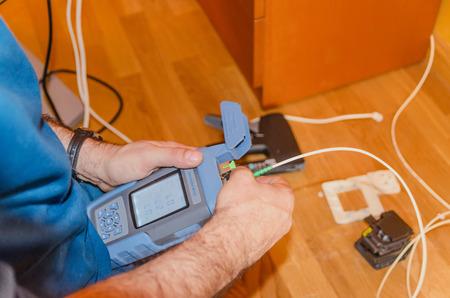 Een technicus meet internet macht na een glasvezel installatie