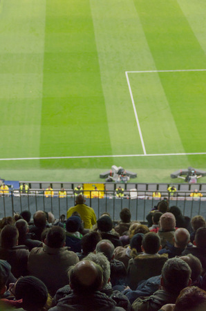 quietly: Football fans are sitting and quietly watching the match