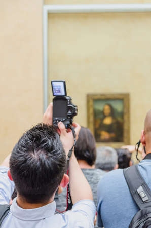 mona lisa: PARIS - SEPTEMBER, 17: Visitors take photo of Leonardo DaVincis Mona Lisa at the Louvre Museum on September, 2014 in Paris, France. Gioconda is one of the worlds most famous pictures in the world.