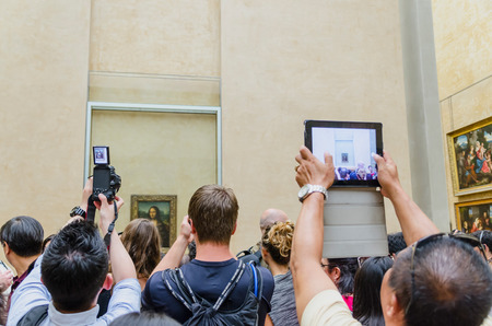 mona lisa: PARIS - SEPTEMBER, 17: Visitors taking photos of Leonardo DaVincis Mona Lisa at the Louvre Museum on September, 2014 in Paris, France. Gioconda is one of the worlds most famous pictures in the world. Editorial