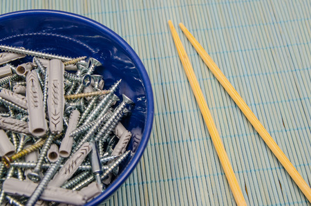 disgusting: A lot of screws and dowels ready to be eaten in a bowl. Impossible food. Disgusting meal