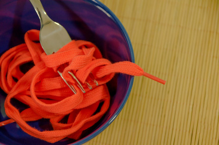 bad diet: Eat time. A blue bowl with shoestrings. Disgusting meal and impossible food concept Stock Photo
