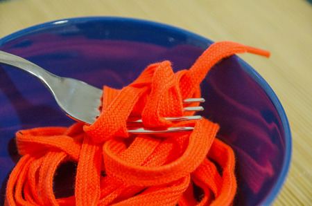 disgusting: A fork with a shoestring in a blue bowl. Disgusting food concept.