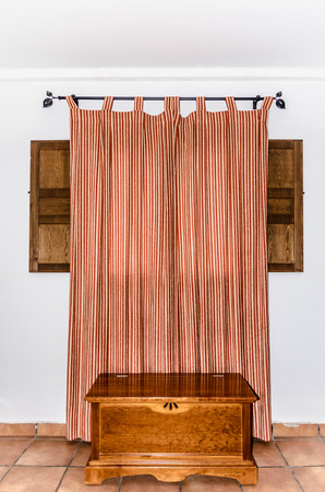 draped cloth: Rustic style decoration in a room. Closed curtain on a wooden window. Typical rural style in spain