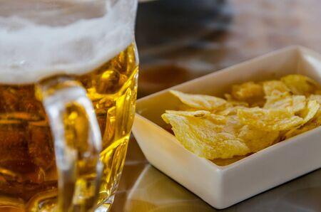 jarra de cerveza: Una jarra de cerveza fr�a con patatas fritas Foto de archivo
