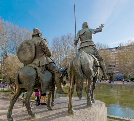 don quijote: Don Quijote a Sancho Panza guía por las calles de madrid. Vista posterior de la escultura de don Quijote en la Plaza de España, Madrid
