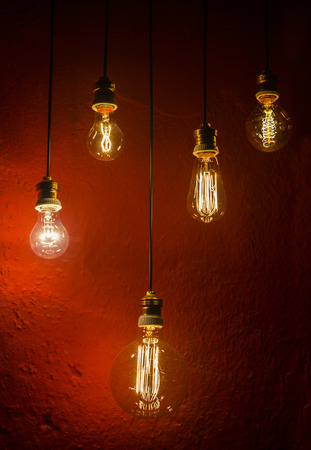 old incandescent lamps lighting together on a wall. Electrical incandescent bulb was a Thomas Alva Edison invention photo