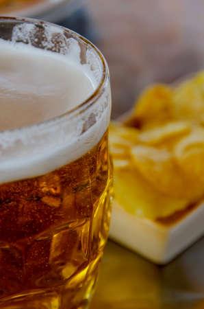 jarra de cerveza: Cierre de vista de una jarra de cerveza con patatas fritas