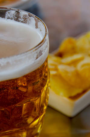 Close up view of a jar of beer with fried potatoes photo