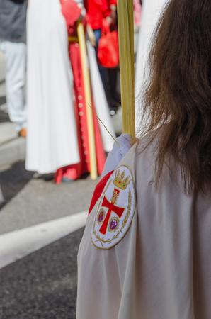 semana: A brotherhood sister holds a palm in a procession. Semana Santa Stock Photo
