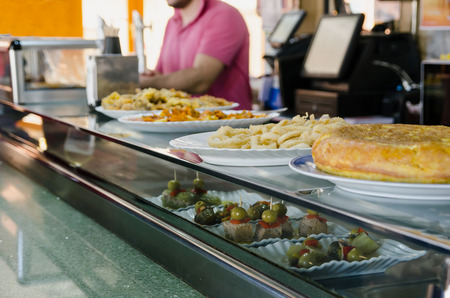 Typical spanish tapas and pinchos in the bar. Potatoes omelette, fried squid, cucumbers, tuna, olives and banderillas