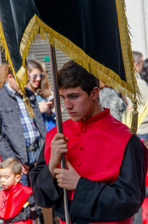 devote: VALLADOLID - 29 MARCH: A penitent holds a brotherhood pennant on March 29, 2015 in Valladolid, Spain. Valladolid has some os the most famous processions in the spanish sacred week