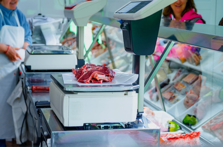 weighs: butcher weighs the raw meat on the market