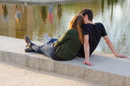 amantes: joven pareja en el amor que se sienta en el suelo parque cerca del agua. El verano es la mejor época para el amor