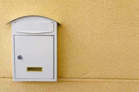 buzon: Buzón metálico pintado en blanco sobre un fondo amarillo