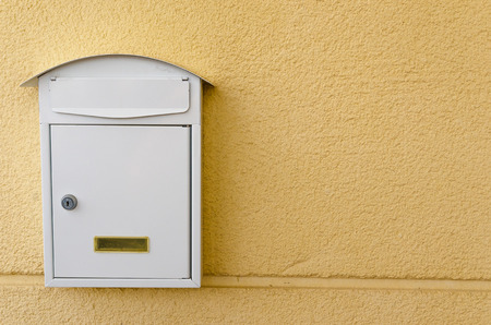 Metallic mailbox painted in white over a yellow background
