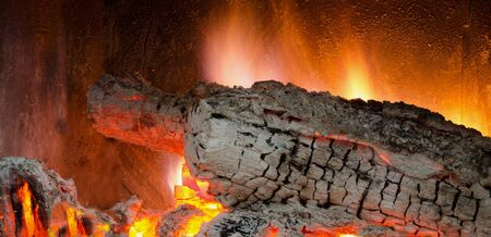 hellish: Burning embers of wood logs in a fireplace Stock Photo